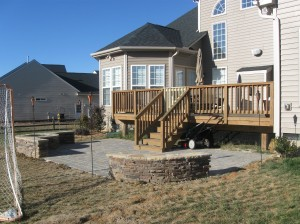 Deck and stone patio with firepit and retaining walls by Archadeck of Charlotte