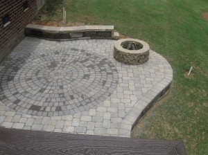 stone patio with outdoor firepit and stone sitting wall