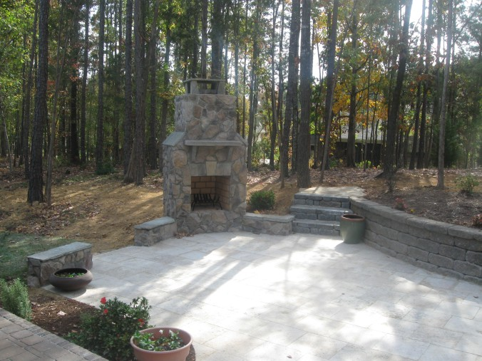 Stone outdoor fireplace with stone travertine patio