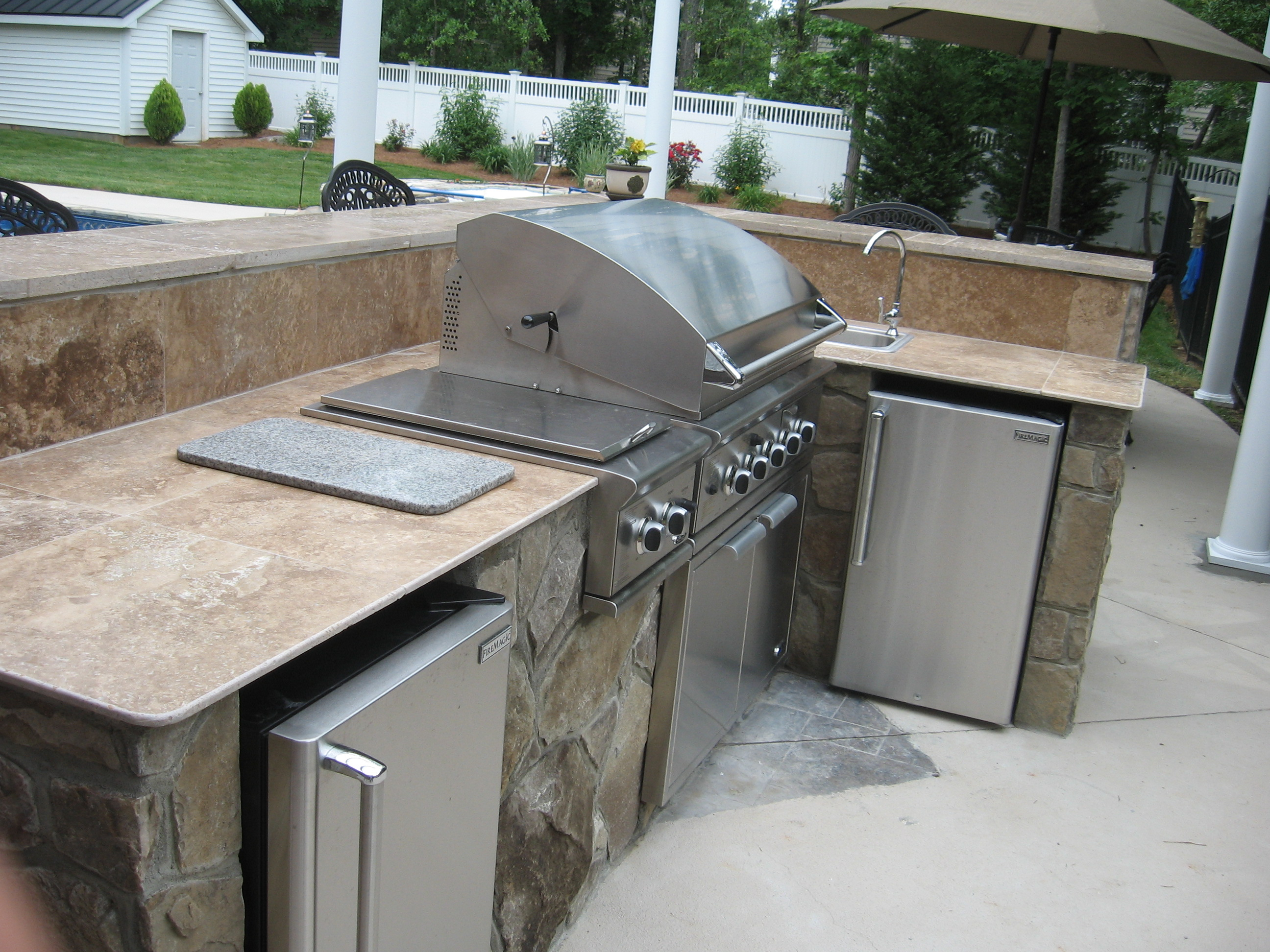 stone outdoor kitchen charlotte with travertine countertop define an outdoor kitchen and what should it cost    archadeck of      rh   charlotte screenporch outdoorfireplace patio com
