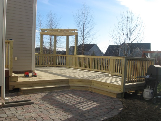 Pavestone paver patio below Cox brand pressure-treated wood deck