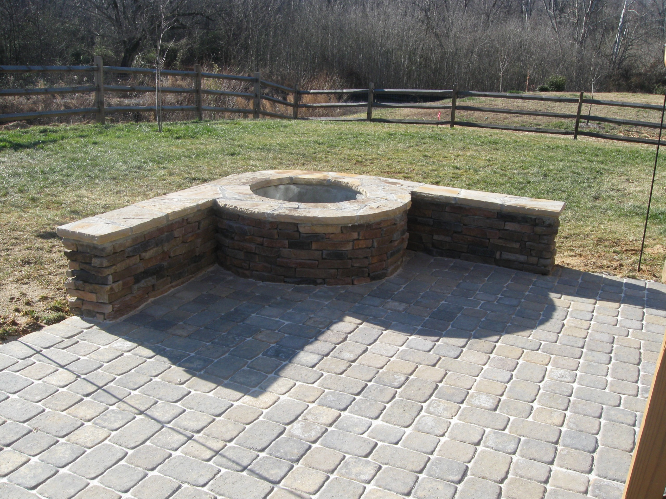 designed an built this stone paver patio with a stone outdoor fire pit