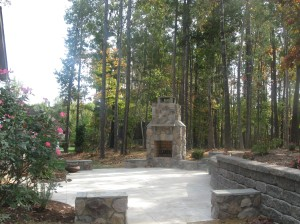 Travertine patio in Charlotte with outdoor fireplace by Archadeck