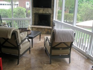 Beautiful screen porch by Archadeck of Charlotte with Travertine tile and an outdoor fireplace integrated into the porch