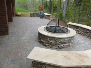 Paver patio with wood burning fire pit and cover on it and stone sitting wall