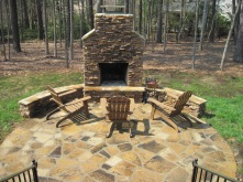 Archadeck of Charlotte designed and built this outdoor fireplace on a flagstone patio with dual sitting walls