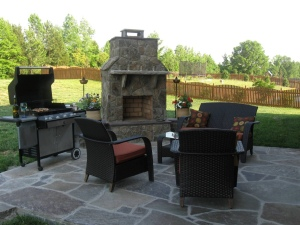 wood burning stone outdoor fireplace with fieldstone on a flagstone patio in Charlotte