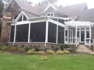 Archadeck screen porch with pergola, outdoor fireplace and stucco skirting