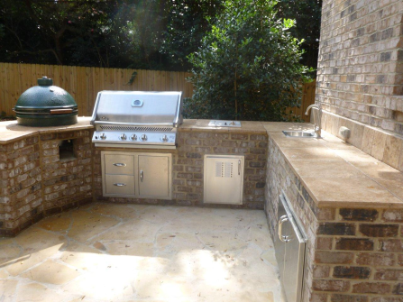 Archadeck of Charlotte designed and built outdoor kitchen with Green Egg, Fire Magic Grill, Travertine counter, outdoor sink, and outdoor refrigerator