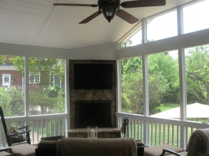 Stone outdoor fireplace in sunroom by Archadeck of Charlotte with a Travertine tile floor