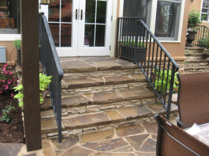 Archadeck of Charlotte designed and built this flagstone patio with black aluminum rail and patio steps