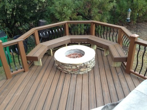 Archadeck of Charlotte built this Trex Transcends Spice Rum composite deck with a composite bench and stone fire pit that is gas burning