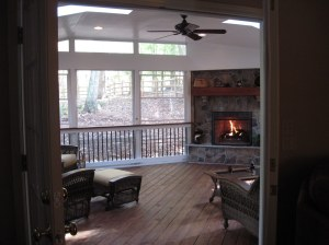 A beautifully integrated outdoor fireplace in a screen porch with EZE Breeze windows in Charlotte, NC on stained pressure-treated wood decking by Archadeck of Charlotte