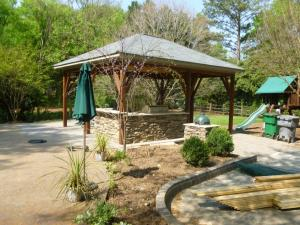 Pool pavilion with a stone box for a Green Egg and outdoor living space built by Archadeck of Charlotte