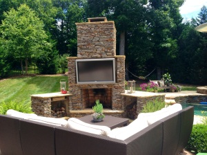 Archadeck of Charlotte designed and built this outdoor living space featuring a Sunbrite outdoor TV and stone outdoor fireplace