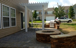 Paver Patio with ledge stone fire pit and sitting wall and a wood pergola with an outdoor kitchen in Ft. Mill, SC by Archadeck of Charlotte