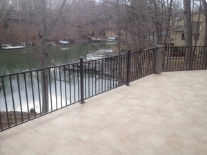 Travertine Tile stone deck with iron rail by Archadeck of Charlotte
