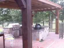 Archadeck of Charlotte designed and built this cedar pergola in south Charlotte with a fieldstone outdoor kitchen and Green Egg