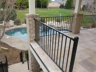 Travertine stone raised porch with metal rail and brick columns in Waxhaw, NC with a pool