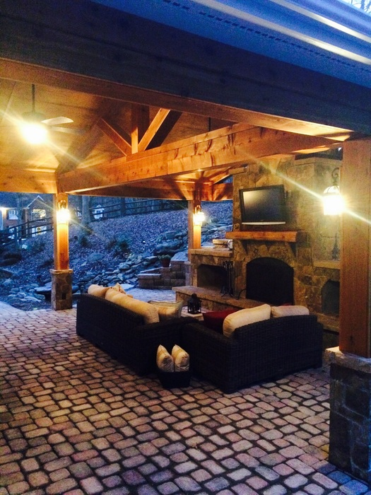 Rustic covered patio with exposed rafters and an outdoor fireplace with stone on columns by Archadeck of Charlotte