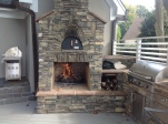 Custom outdoor fireplace and pizza oven with an outdoor kitchen on a Trex Transcends Gravel Path deck on Lake Wylie in South Carolina by Archadeck of Charlotte