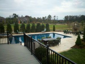 Archadeck of Charlotte designed and built this Travertine tile pool deck as well as the stone outdoor fireplace in Waxhaw, NC