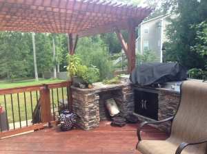 Pressure-treated wood deck stained with pergola and outdoor kitchen by Archadeck of Charlotte