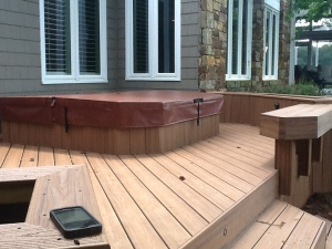 Trex Transcends composite deck with a hot tub recessed onto a cement pad and composite beching for the ideal