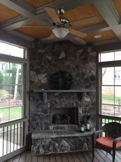 Stone outdoor fireplace integrated into screen porch with EZE Breeze windows